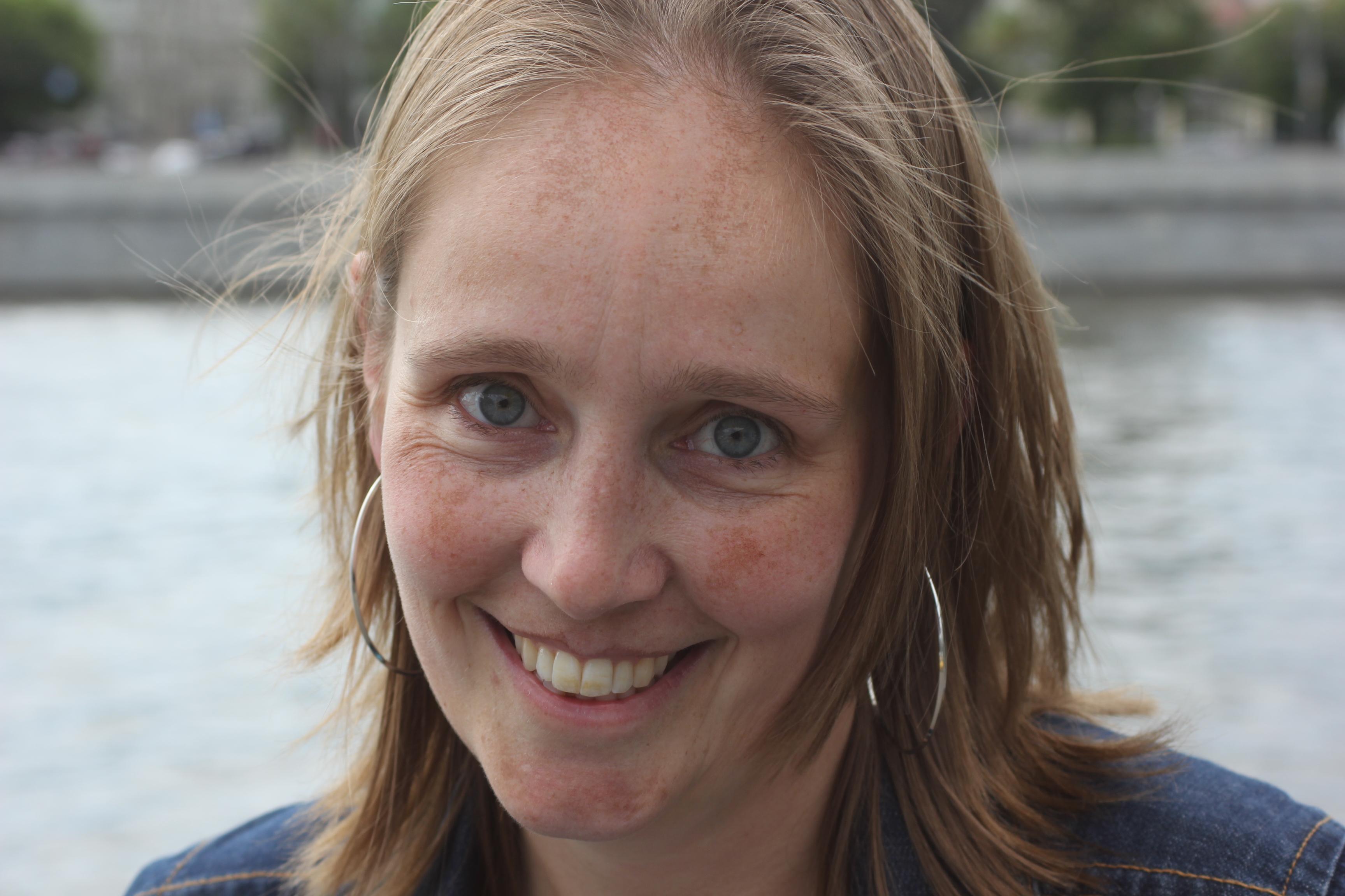 Een vrouw met schouderlang haar kijkt recht in de camera en glimlacht haar tanden bloot. Ze draagt grote zilverkleurige ringen in haar oren.