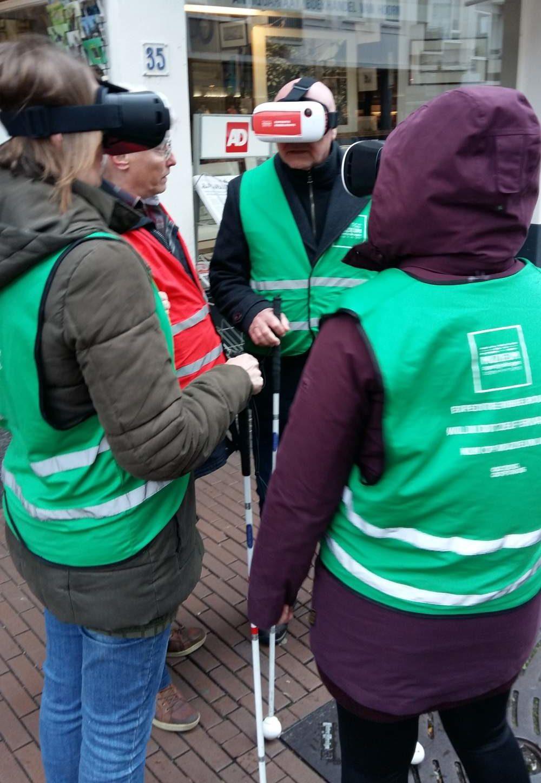 Een groep van 4 mensen die in een kring taan met hun gezicht naar elkaar. Ze dragen waarschuwingshesjes, houden een geleidenstok vast en hebben een VR bril op hun hoofd.