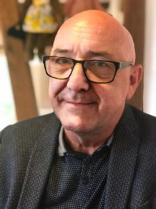 Een glimlachende kalen man met bril met donker montuur in een donker grijze colbert met eveneens donkergrijze blouse