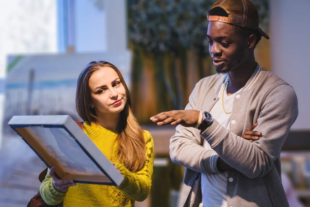 Een Afrikaans uitziende man en Europees ogende dame bekijken samen een kunst werk terwijl ze er over praten