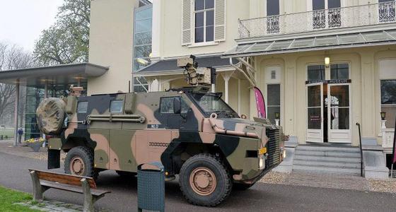 Voor het zandkleurige gebouw staat een militair camouflage voertuig
