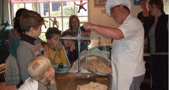 Een groep kinderen staat geïnteresseerd te kijken en luisteren naar een bakker die brood weegt met een ouderwetse weegschaal met gewichten.