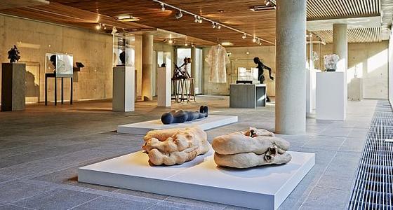Een foto van de lichte grote zaal met stenen vloer en pilaren waar tussen op plateaus diverse kunstwerken zijn gepositioneerd in de ruimte