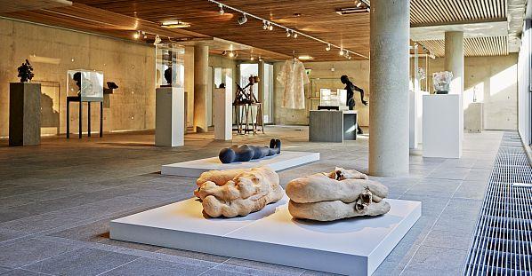De binnenzaal van Museum Beelden aan Zee met op witte plateaus en sokkels sculpturen en beelden