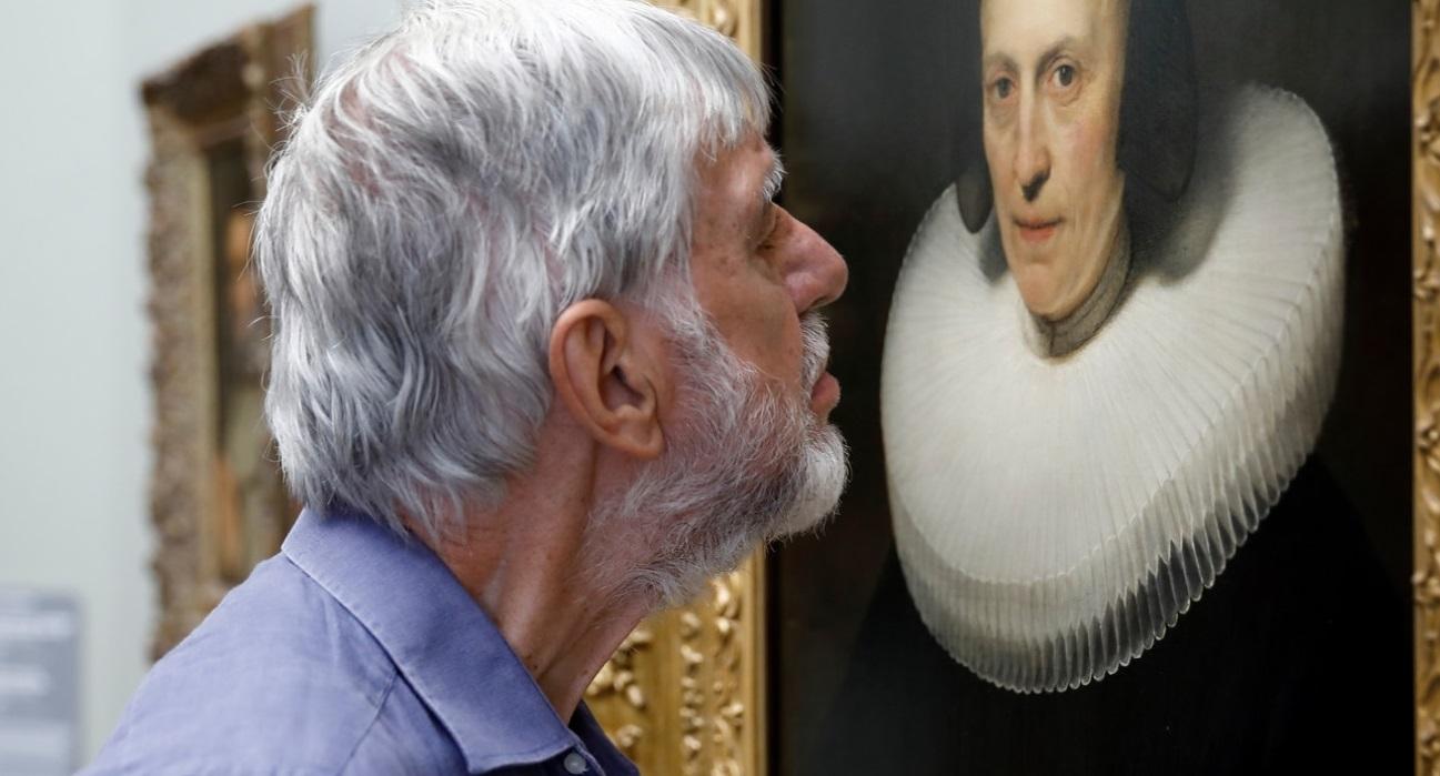 Een man met baard en snor staat met bijna zijn neus op een schilderij om deze goed te bekijken