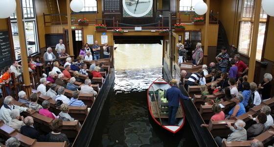 De veilingzaal met in het midden het water waar de boten met goederen doorheen varen en daarboven de veilingklok. Links en rechts de banken met de mensen die willen bieden op de goederen.