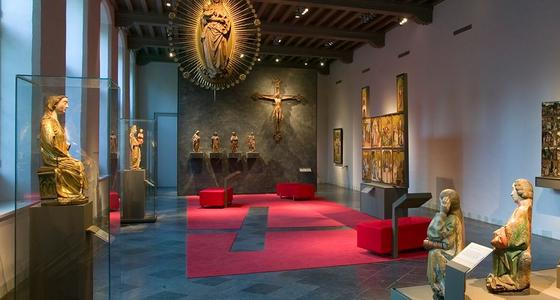 In een grijze expositieruimte springen de goedkleurige religieuze beelden er duidelijk uit. Ze zijn goed uitgelicht in hun vitrines en tegen de wanden. Op de vloer ligt een rood kleed en staan rode vierkante krukken.