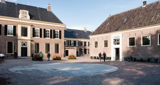 Een statig lichtbruin bakstenen gebouw met 2 hoge verdiepingen en grijzen dak. De ingang ligt aan een rustig plein