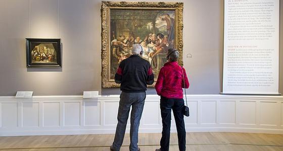 Een man en vrouw staan voor een schilderij met rechts daarvan een tekst en links een kleiner schilderij. Ze hebben allebei een koptelefoon op hun hoofd.