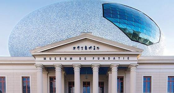 Een grieks aandoende tempel is de voorgevel van museum de Fundatie. Op het dak een grote lichtblauwe eivormige koepel met blauw glazen raam erin.