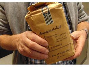 Twee handen houden een bruine papieren zak vast met daarin amateurtabak