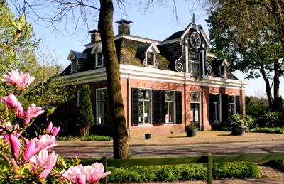 Het museumpand op een zonnige dag, met roze bloemen en een groen grasveld op de voorgrond