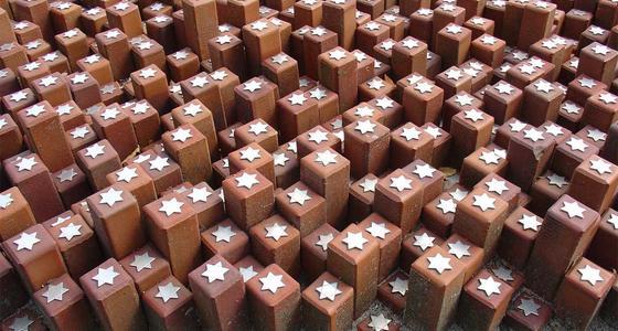 Bruine tegen elkaar geplaatste vierkante paaltjes van wisselende hoogte, met bovenop elk paaltje een witte 6 hoekige ster