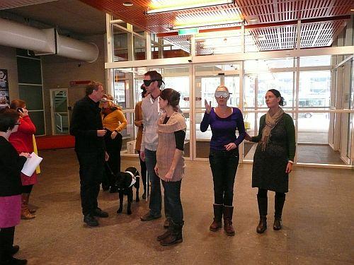 Een groep mensen met simulatiebrillen op hun neus staan in de hal van et museum