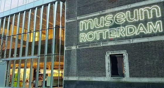 De voorgevel van het museum met glazen pui en en daarnaast de stenen muur met in neonletters de tekst Museum Rotterdam