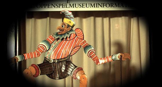 Een stokpop van arabisch ogend mannelijk figuur voor een theatergordijn waar een grote schijnwerper op schijnt waardoor het tafereel in een cirkel lijkt te staan en de randen zwart vervagen.