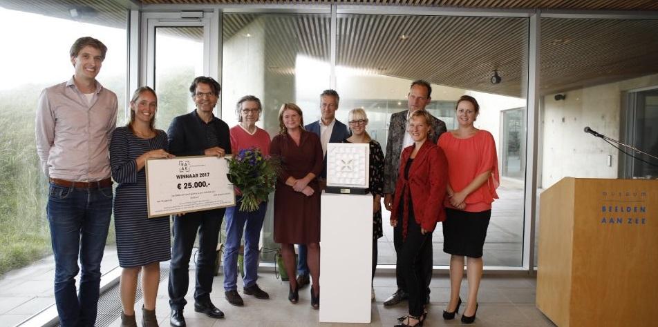 De winnaars van de prijs met organisatie van de prijs samen op een foto met de check en de bloemen