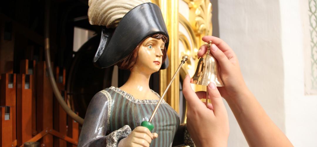 Een detail van een draaiorgel waarop een van de vrouwelijke figuren is te zien die met een stokje tegen een belletje tikt