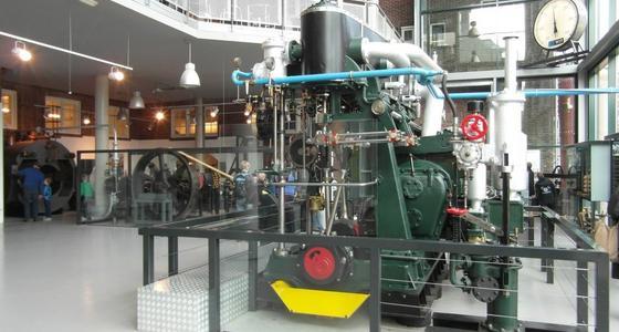 Museumzaal met vide en grote hoge ramen met daarin een grote groene machine met pijpen en stuurwielen.