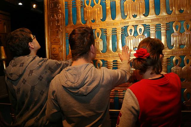 3 mensen voelen aan een blauwe wand met daarop gouden hiërogliefen