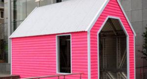 Een knal roze houten huisje met wit dak, vormt de entree naar het restaurant