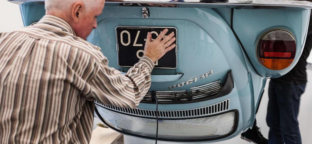 Een man voelt aan de achterkant van een auto, een ouderwetse eend, deze hangt alleen ondersteboven
