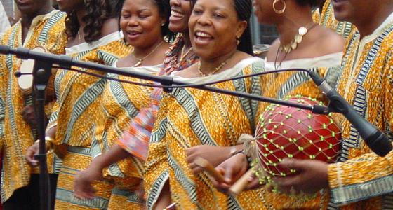 Afrikaanse vrouwen in gele traditionele jurken zingend achter een microfoon