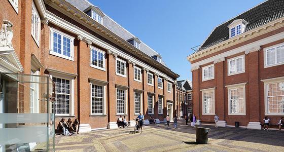 Het plein met het daaraan gelegen elegante bakstenen gebouw van het museum. De ramen zijn groot met kleine ruitjes in witte kozijnen .