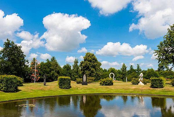 Aan de overkant van het water is een grasveld met struiken en verder naar achter bomen. Op het grasveld staan verschillende beelden en sculpturen.