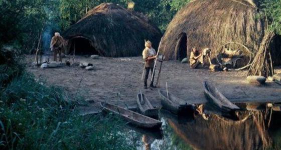 Een historische verbeelding van rieten hutten op een kaal terrein met houten kano's die op de kant liggen en prehistorische mensfiguren.
