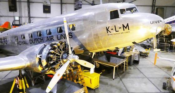De voorkant van een glimmend zilveren oud vliegtuig met proppelors in de vleugels en zwarte belettering