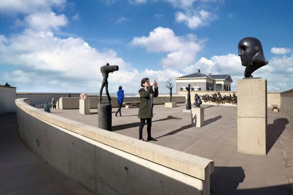 Een vrouw maakt een foto op een van de buiten terrassen van het museum waar verschillende beelden zijn tentoongesteld op sokkels
