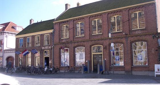 Het donkerrode bakstenen gebouw met grijze dak en cremekleurige vensters en dakgoot is in hetzelfde pand gevestigd als de VVV