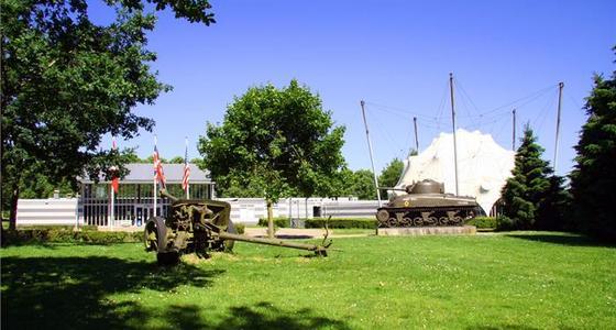 Buiten op het terrein bij het museum staan op het gras twee tankwagens tentoongesteld.