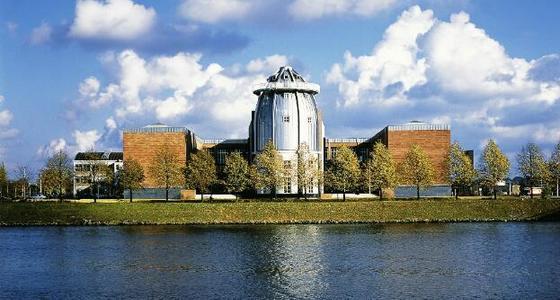 Aan de overkant van het water ligt het museum in de zon. Een grote metalen ronde toren loopt taps toe in een punt, Aan beide zijde wordt de toren vergezeld door rood bakstenen blokken.(gebouwen zonder ramen)
