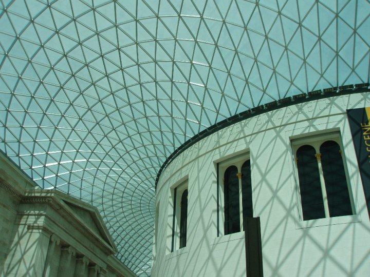 Een foto van het glazen dak van het musuem vanaf de binnenzijde genomen. Rechts een ronde witte zaal