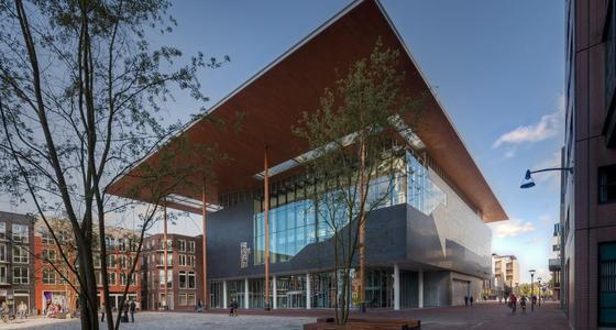 Het modern aandoend gebouw is grotendeels van glas en heeft een groot uitstekend plat dak