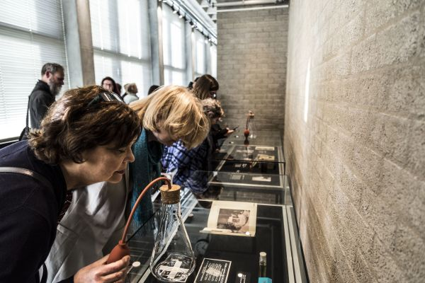 mensen buigen zich over vitrines waar parfumflessen op staan om geuren te kunnen ruiken die bij de attributen in de vitrine passen.