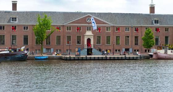 De voorkant van het gebouw de Hermitage aan het water. Het langgerekte stenen gebouw met grijs pannendak is aangekleed met Amsterdamse vlaggen.
