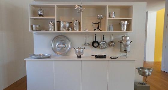 In een witte open kast staan, liggen en hangen verschillende zilveren keukenspullen zoals lepels, kannen, schalen en pannen.