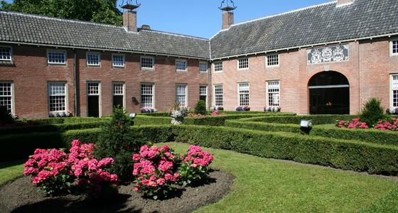 De binnenplaats van het hofje is groen gekleurd door de heggen en grasveldjes met daarin rozenperkjes. Het gebouw is van licht oranje bakstenen met een grijs pannen dak.