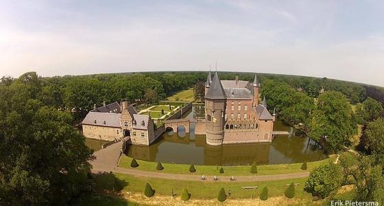 Een luchtfoto van het kasteel met binnen de kasteelmuren een hoog bruin stenen kasteel met zilver grijzen daken, ronde torens en groene tuinen.