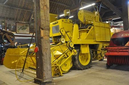 In een grote hoge houten schuur staat een grote gele landbouwmachine