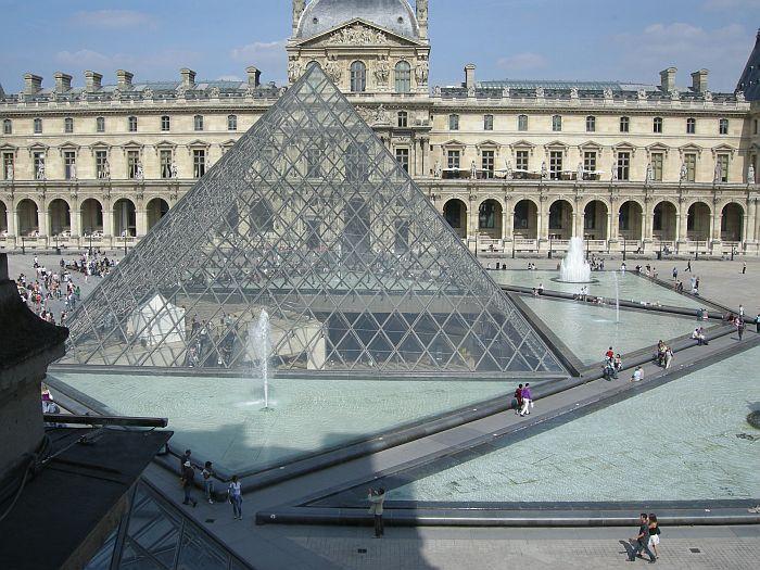 een foto van de glazen piramide met op de achtergrond het zandstenen gebouw van het museum