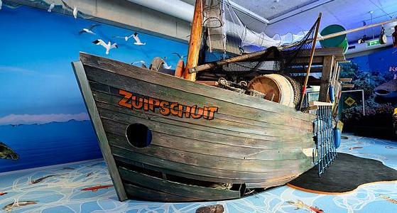 """Op de romp van een groot houten schip staat in oranje letters """"Zuipschuit"""", op de boot liggen tonnen en er hangen netten aan de mast. Op de vloer is een zee geschilderd en er hangen meeuwen boven de boot."""
