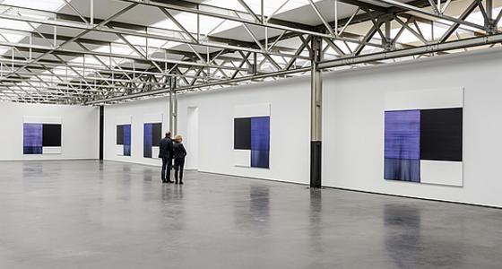 Een grote open zaal met witte paneelwanden met schilderijen erop. De vloer glimt en het dak is licht en bestaat uit een metalen frame