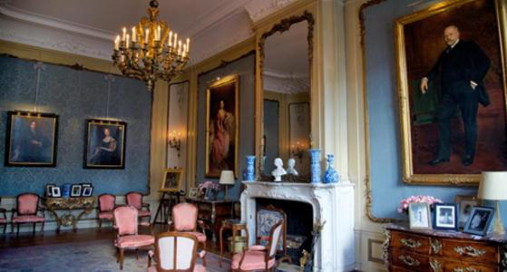 In de kamer met blauwe muren staat luxe meubilair, roze sjieke stoelen en gedecoreerde kasten. Aan de muur hangen grote schilderijen van mensen