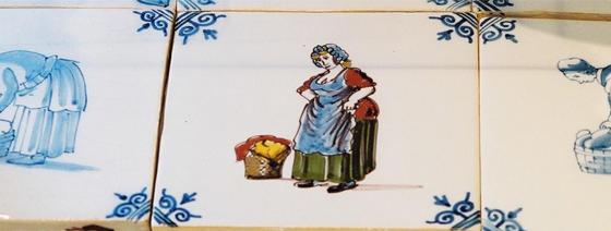 een keramieken tegel met daarop blauwe versieringen in de hoeken en in het midden een vrouw in werkkleding die haar schort ophoudt, naast haar staat een mand met wasgoed.