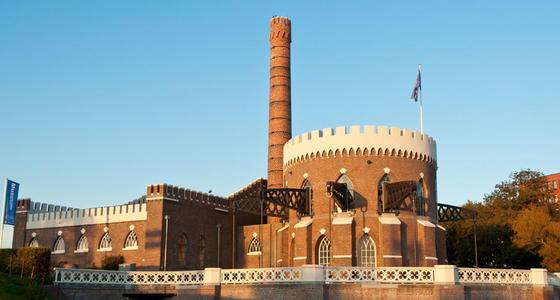 Het museum met roodstenen muren en witte kantelen in de ondergaande zon. Het gebouw kenmerkt zich door zijn ronde toren en hoge schoorsteen.