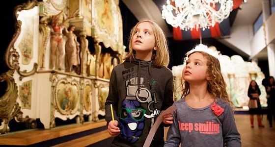 Twee kinderen lopen langs een groot goudkleurig draaiorgel. Ze kijken vol verbazing schuin omhoog naar het orgel met al zijn kleine details.